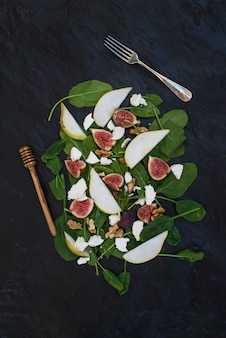 Salad with pears, baby spinach, figs, walnuts, goat cheese and honey on black stone  table