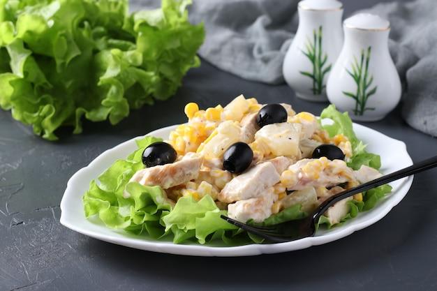 白いプレートにパイナップル、焼きチキン、コーン、ブラックオリーブのサラダ