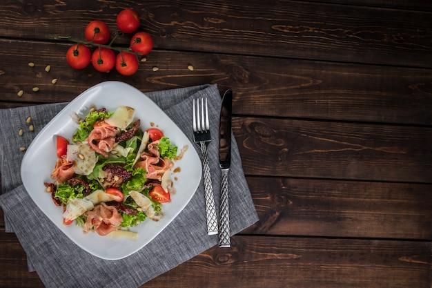Салат с прошутто и пармезаном. помидоры черри, столовые приборы, ножи, вилки и кедровые орехи на столе. плоское горизонтальное фото. свободное место для текста