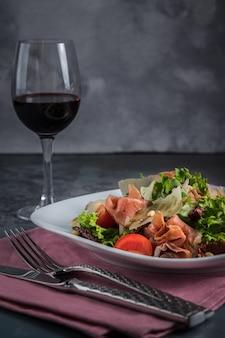 Салат с прошутто и пармезаном. столовые приборы, ножи, вилки и розовые салфетки на сером фоне. бокал красного вина