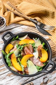 Salad with prosciutto crudo, arugula, peach and parmesan
