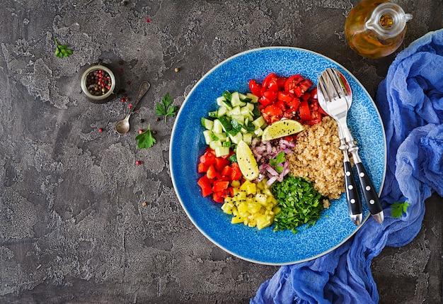 キノア、ルッコラ、ピーマン、トマト、暗いテーブルのボウルにキュウリのサラダ。健康食品、ダイエット、デトックス、ベジタリアンのコンセプトです。仏丼。上面図。フラットレイ