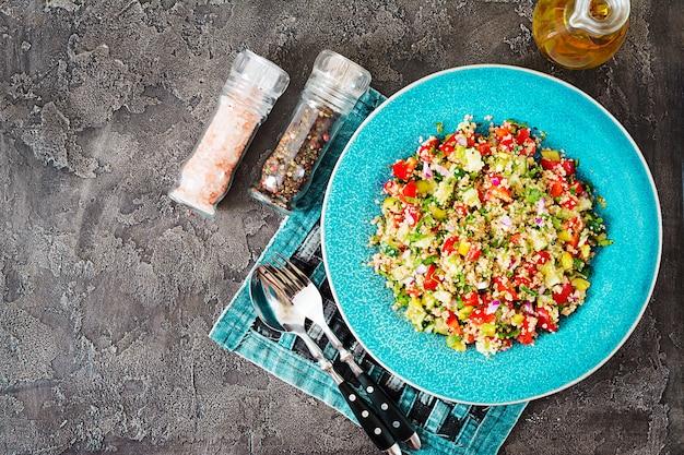 キノア、ルッコラ、ピーマン、トマト、暗いテーブルのボウルにキュウリのサラダ。健康食品、ダイエット、デトックス、ベジタリアンのコンセプトです。タブーラサラダ。上面図。フラットレイ
