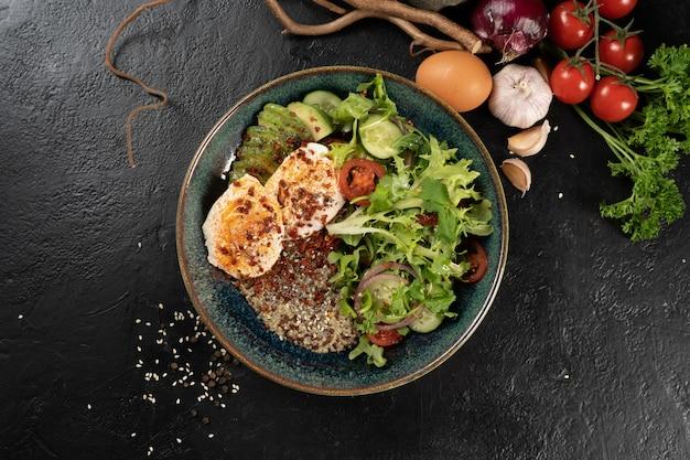 Салат с киноа, авокадо, яйцом-пашот и овощами. холодная острая вегетарианская закуска