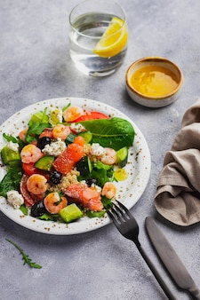 キノア、アイスバーグレタス、ルッコラ、キュウリ、ブラックオリーブ、トマト、カッテージチーズ、サーモン、エビ、マンゴーソースのサラダ。免疫のためのきれいな食事
