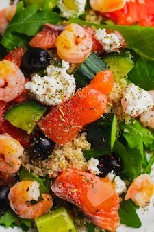 Salad with quinoa, iceberg lettuce, arugula, cucumber, black olives, tomato, cottage cheese, salmon, shrimp and mango sauce