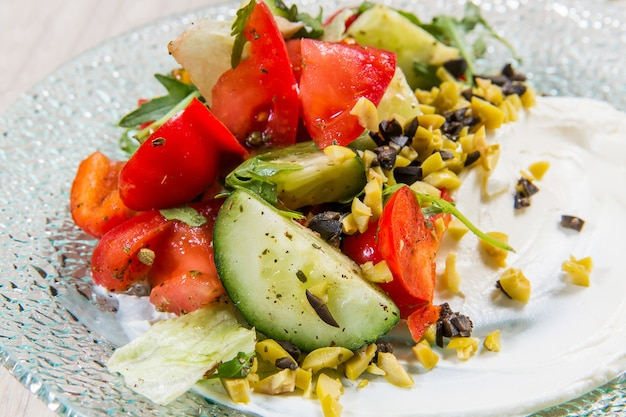 Salad with red tomatoes, cucumbers and olives in glass plate on light table in a restauran