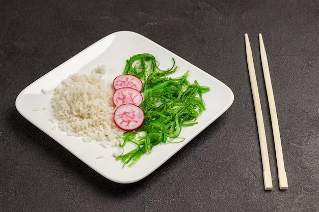 ご飯、大根、海苔の白い皿のサラダ。アジア料理。竹箸