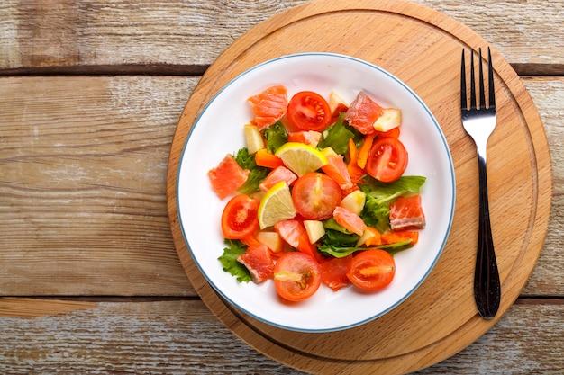 Салат с лососем и помидорами черри и зеленым салатом в тарелке на деревянном столе на деревянной подставке рядом с вилкой