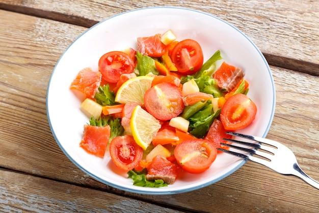 Салат с лососем и помидорами черри и зеленым салатом в тарелке на деревянном столе с вилкой.