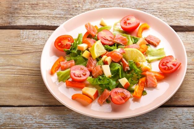 Салат с лососем и помидорами черри и зеленым салатом в тарелке на деревянном столе