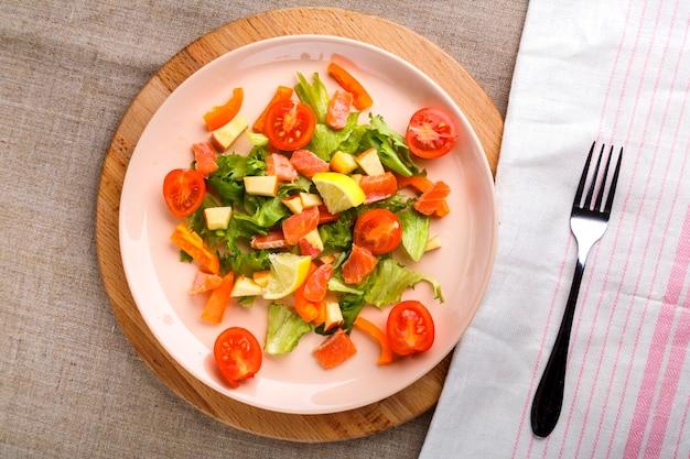 Салат с лососем и помидорами черри в тарелке на серой поверхности на деревянной подставке рядом с вилкой и салфеткой