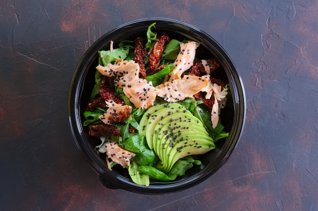 Salad with salmon, avocado and sun dried tomatoes in take away packaging