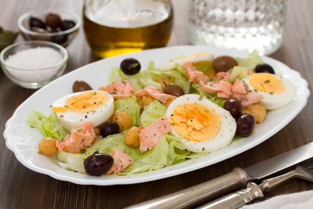 Salad with salmon, eggs and olives on white dish