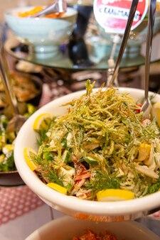 Салат с соусом, овощами и пай картофелем в кафе