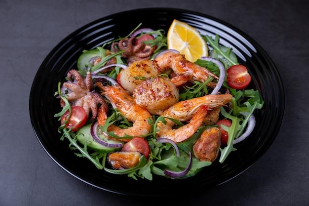 Салат с морепродуктами, рукколой, помидорами, огурцами, красным луком и лимоном на черной тарелке.