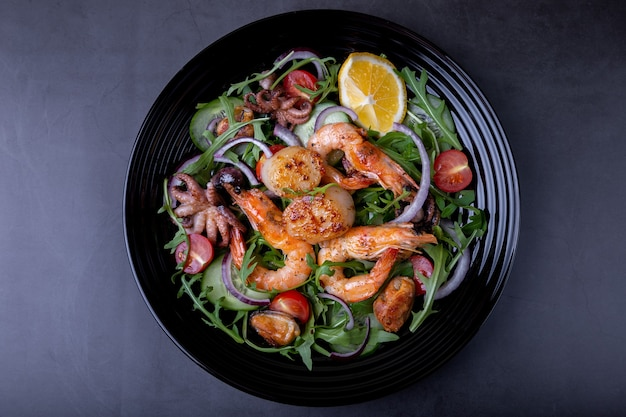 Salad with seafood, arugula, tomatoes, cucumbers, red onion and lemon on a black plate.