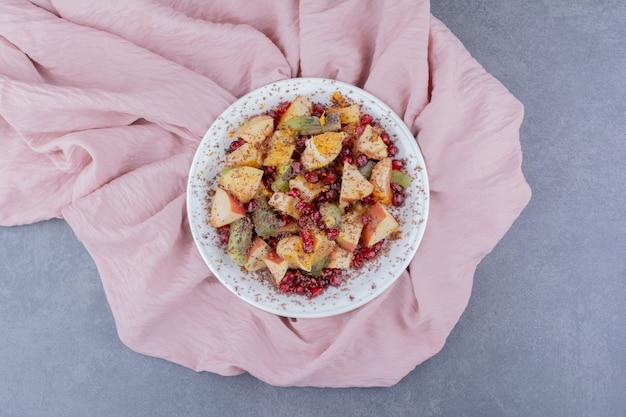 Insalata con frutta di stagione e spezie su superficie in cemento