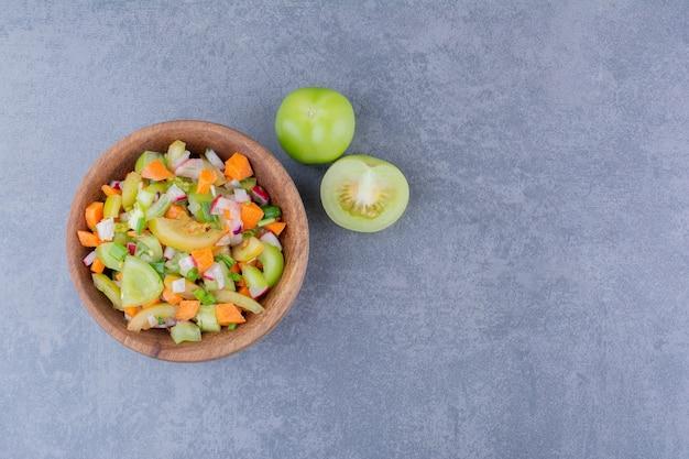 Салат с сезонными зеленью и овощами в миске