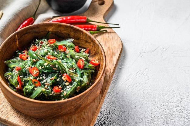 Салат с водорослями вакаме и красным перцем чили. серый фон