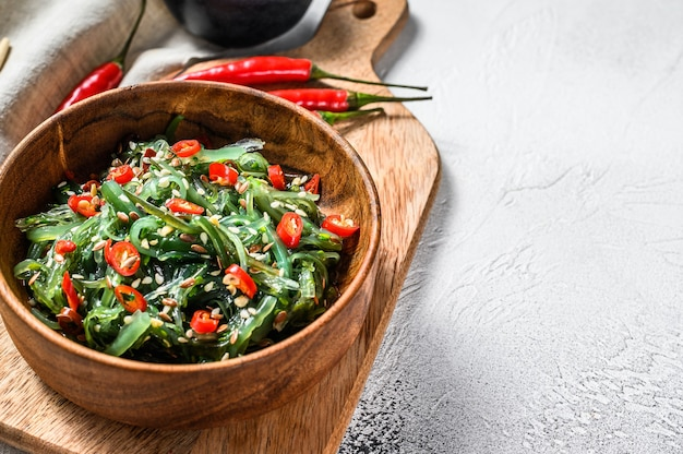 Salad with seaweed wakame and red chili pepper. gray background