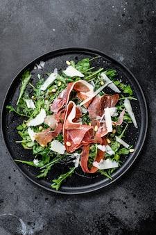 Salad with serrano jamon, ham, rucola and parmesan cheese. black surface, top view.