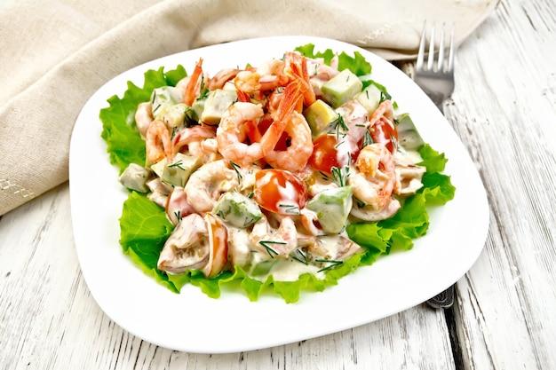 白い皿の緑のレタスにエビ、アボカド、トマト、マヨネーズのサラダ、ナプキン、背景の明るい木のテーブルにフォーク
