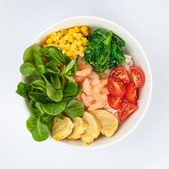 Салат с креветками, помидорами в белой тарелке на белом фоне