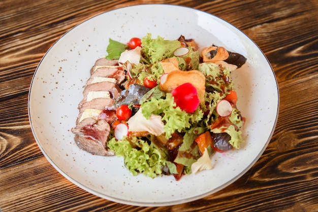 Салат с нарезанным мясом, сыром, овощами и миксом салата на белой тарелке на деревянном столе. аппетитное ресторанное блюдо.