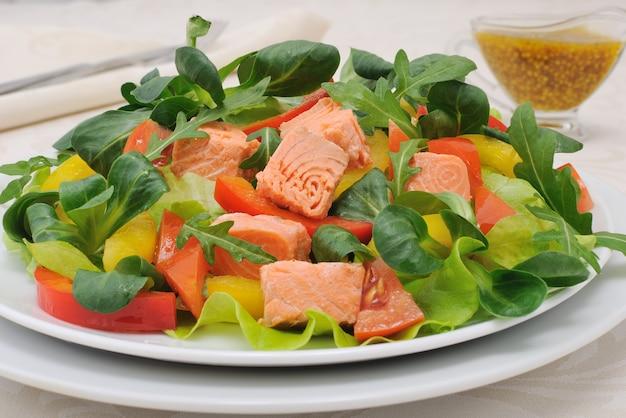 Салат с ломтиками корней лосося, помидорами, рукколой и перцем, заправленный горчичным соусом