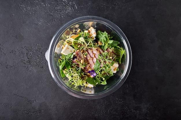 Салат с копченой утиной грудкой, овощами, сыром и зеленью в прозрачной таре на темном