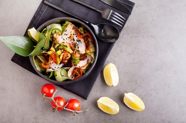 大きな緑の葉で飾られたスモークうなぎのサラダ、ゴマをまぶしたもの。アジア料理のコンセプト。