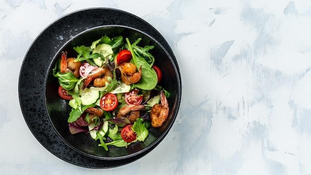 Салат с копчеными креветками, помидорами черри, огурцом и смешанными листьями. концепция морепродуктов. баннер, место рецепта меню для текста, вид сверху.