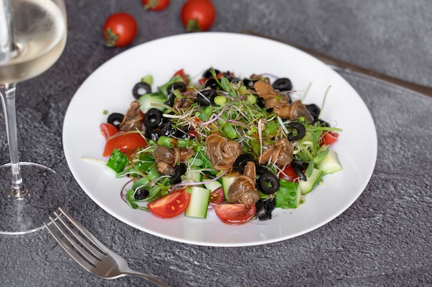 달팽이, 올리브, 토마토 체리, 오이, 어두운 배경에 채소를 곁들인 샐러드.