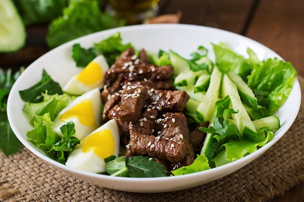 Salad with spicy beef, cucumber and eggs in the asian style.
