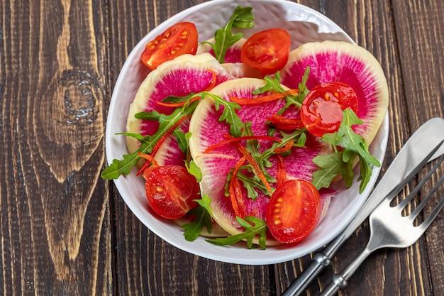 ほうれん草、ルッコラ大根、玉ねぎ、ミニトマトのサラダ。ベーコンサンドイッチ。茶色の背景に。スペースをコピーします。