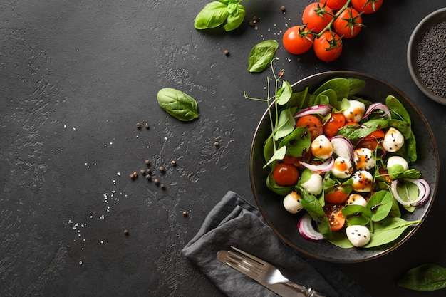 Салат со шпинатом, помидорами черри, луком и моцареллой на черном фоне камень. вид сверху.
