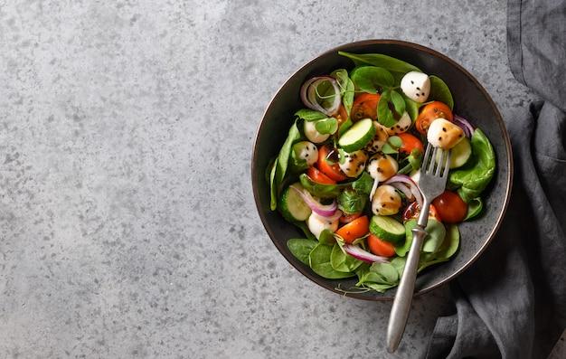 회색 돌 배경에 시금치, 체리 토마토, 양파와 모 짜 렐 라 샐러드. 평면도.