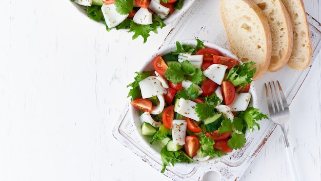Салат с кальмарами, огурцами, помидорами и листьями салата. lchf, fodmap, палео диета. свежий весенний витамин