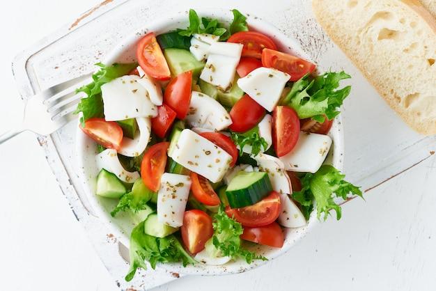 Салат с кальмарами, огурцами, помидорами, листьями салата. lchf, fodmap, палео диета. здоровая средиземноморская еда