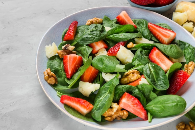 Salad with strawberry, spinach leaves, parmesan cheese and walnuts on concrete table. healthy diet food