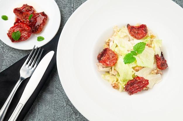 サンドライトマト、白菜、クルミ、パルメザンチーズのサラダ。白いお皿に。フォークとナイフの近く。上からの眺め。灰色のコンクリートの背景に。