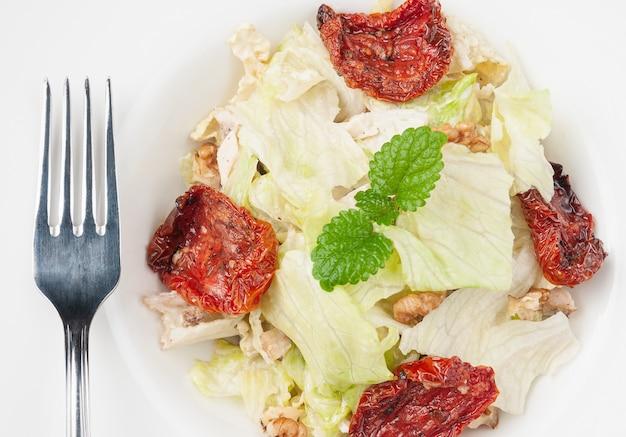 썬드라이 토마토, 북경 양배추, 호두, 파마산 치즈를 곁들인 샐러드. 하얀 접시에. 플러그 근처. 확대. 매크로.