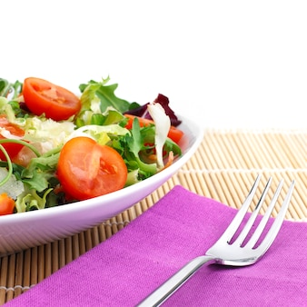 Salad with tomato and cheese over placemat