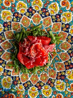 Salad with tomato red onionrugula oil and sesame on plate