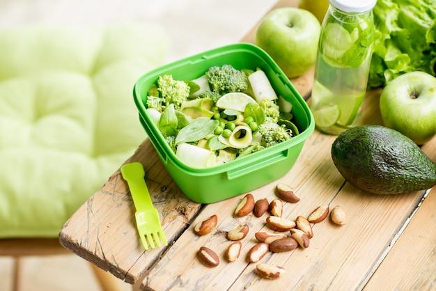緑の健康的な食材を使った木製のテーブルのボウルにトマトとチーズのサラダ。健康食品のコンセプト