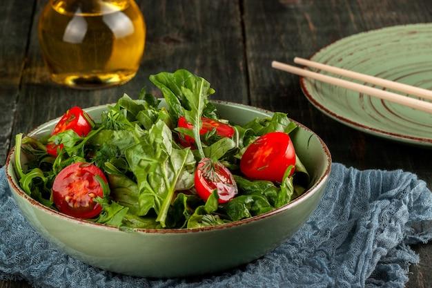 검은 나무 테이블에 토마토, arugula, 시금치 샐러드