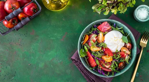 Салат с помидорами, рукколой, сыром буррата и микрозеленью на зеленом каменном фоне, вид сверху. копировать пространство