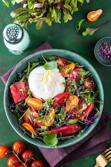 Салат с помидорами, рукколой, сыром буррата и микрозеленью на фоне зеленого камня, вид сверху, вертикальный