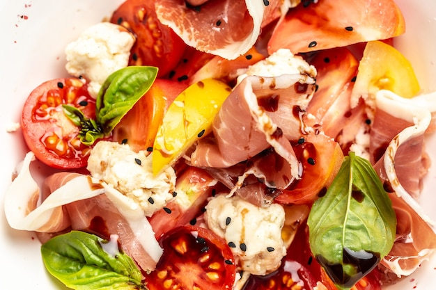 토마토, 크림 치즈 볼, 프로슈토, 바질 잎을 곁들인 샐러드. 음식 조리법 배경입니다. 확대.